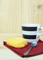 Fresh donut with a coffee cup on wooden table backgrounds vertical side views