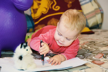 A little child draws with a pen