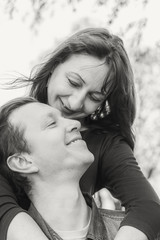Affectionate young couple in park by the river. Love story. Black and white.
