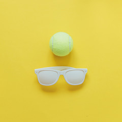white sunglasses and tennis ball on yellow background. minimal concept of summer sport