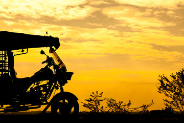 Silhouette of Tricycle in Thailand on sky sunset background