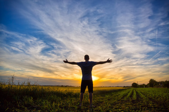 Man standing in an open field at sunset with open arms - embracing nature