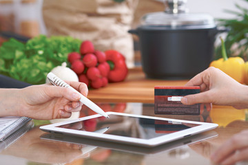 Close-up of four human hands are gesticulate over a tablet in the kitchen. Friends having fun while choosing menu or making online shopping. So much ideas for tasty cooking.