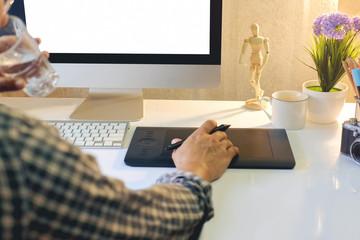 Graphic designer using digital tablet and modern desktop computer.