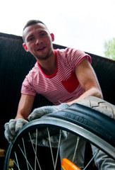A young guy fixing a wheel from a bicycle