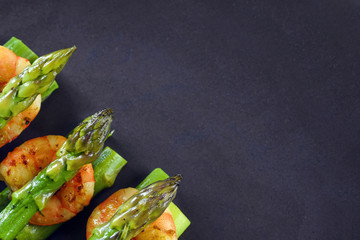Stores à enrouleur Entree green asparagus with tiger prawn shrimp on a dark gray plate, top view from above with large copy space, festive appetizer or buffet snack