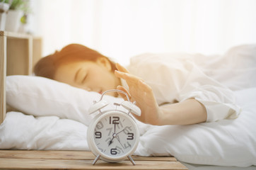 Sleepy asian young woman in bed with eyes closed extending hand to alarm clock at home.