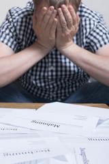 Person ohne Perspektive mit Rechnungen auf dem Tisch vor sich