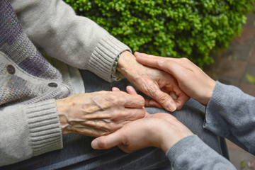 Touches the hands of an old woman - Concept of Elderly care