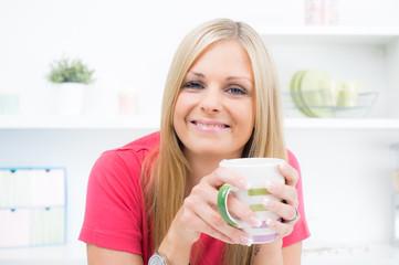 Hübsche Hausfrau ist glücklich bei einer Tasse Kaffee