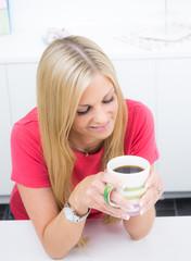 Nette Hausfrau in Gedanken mit einer Tasse Kaffee