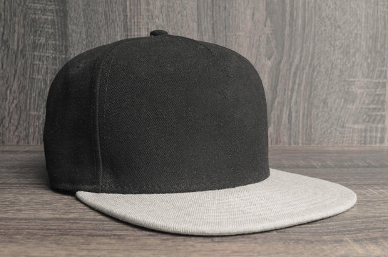 Black cap with light gray flap on a wooden background. Straight flap caps with no brand.
