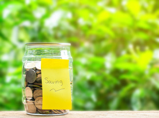 Coins in jar and stick label that saving on wooden table and nuture background