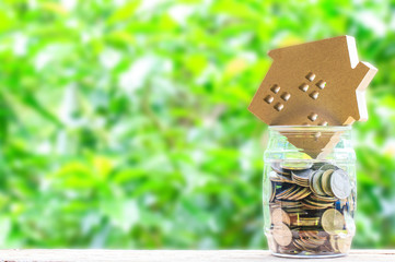 Paper house, Coins in jar on wooden table and nuture background