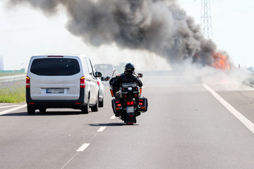Car crash / accident / road disaster concept. Vehicles passing a car burning with a thick black smoke on the highway
