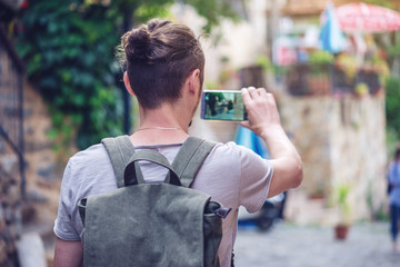 Man backpack makes a photo on your smartphone on a city street