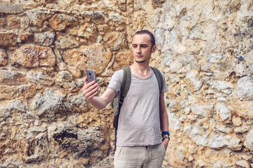 Man traveler with backpack makes a photo on his smartphone on the background of a stone wall