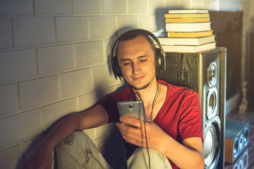 Attractive young man listening to the audio book in the headphones. Concept of technology education a positive lifestyle