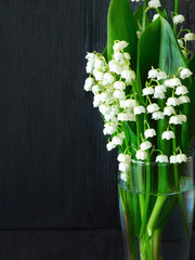 Lily of the valley bouquet in a glass vessel on a dark background