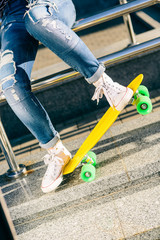 Close up of woman's legs in jeans and white sneakers on penny board skateboard. Sit on railings and have fun. Modern urban hipster girl have fun. Good sunny summer day for lifestyle skateboarding.
