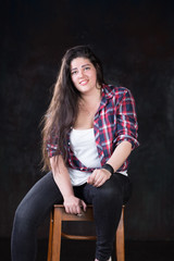 Plus size model with dark hair in a casual style on a dark background at a photo studio