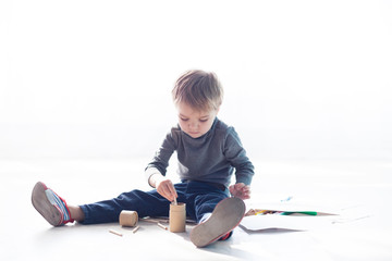 little boy paints a picture of crayons