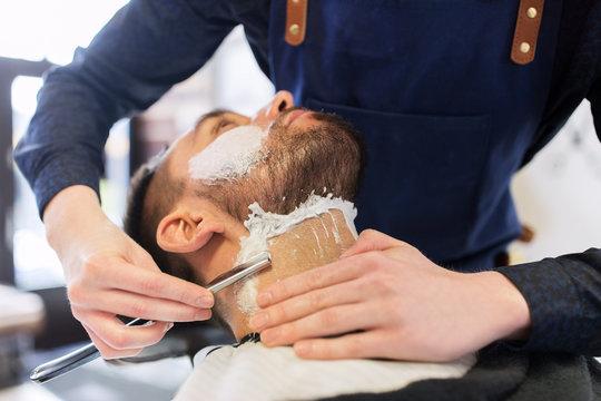man and barber with straight razor shaving beard