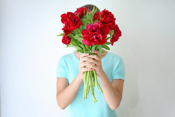 Young woman holding bunch of peonies on white background