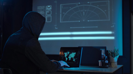 Man in the hood from his back sitting and working at laptop as hacker, with world map on wall in background. Then he take off usb flash disk and run away. Perhaps he has stolen information or has