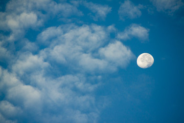 The moon with white cloud on the blue sky.