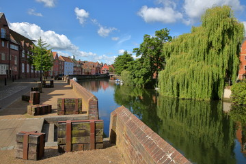 The riverside (river Wensum) in Norwich (Norfolk, UK) with colorful houses on the left side and the Fye Bridge in the background