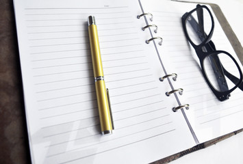 Eye Glass on Diary with Golden Pen