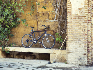 black  bicycle parked on the stone wall