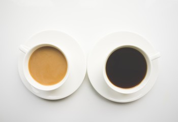 Cup of coffee with milk and black on a white background. Top view
