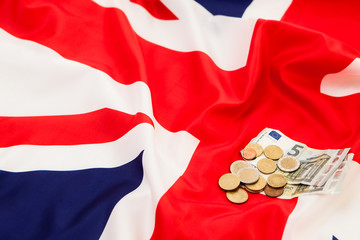 Bribe Euro currency and coins lie on the background of the flag of Great Britain.