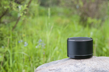 Bluetooth speaker standing on a big stone over nature background.