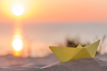 Yellow paper boat on a beach at sunrise