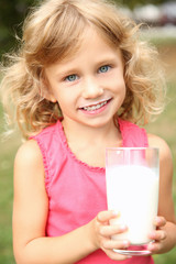 Portrait of cute little girl with glass of milk, closeup
