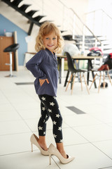 Cute little girl wearing her mother's shoes