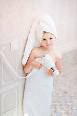 Little beautiful girl in a towel in the bathroom with a hair dryer