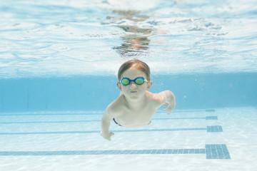 Boy (6-7) swimming in pool