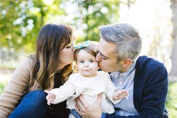 Portrait of parents kissing daughter (12-17 months) in park