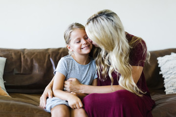 Woman giving daughter (6-7) cheek kiss