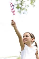 Smiling girl (4-5) holding american flag