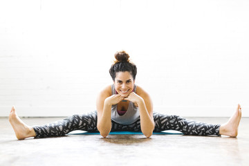 Portrait of woman stretching on exercise mat
