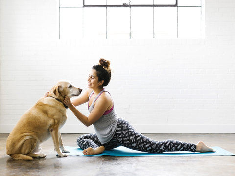 Woman pampering dog while doing yoga in the gym