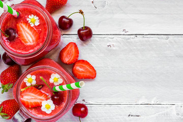 strawberry and cherry smoothie in glass jar with a straw and fresh fruits and berries