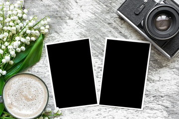 vintage retro camera with blank photo frames to put your pictures and coffee cup with lily of the valley flowers