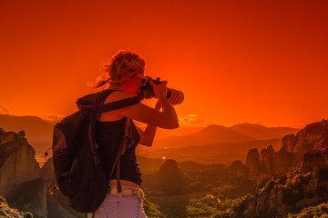 Traveler woman photographer with telelens takes photos of rock monasteries Meteora, Central Greece, Europe. Female photographer takes picture outdoors. Sunset light. Scenic travel destination.
