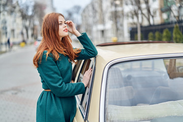 A woman stands by the car, a woman leans on a car